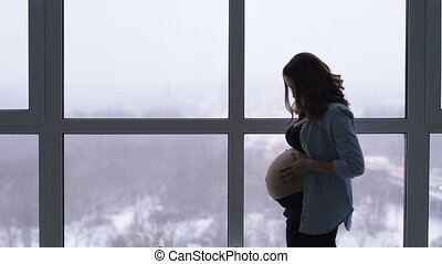 A happy pregnant woman stands at a large panoramic window...