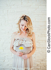 a happy  pregnant woman with yellow flower