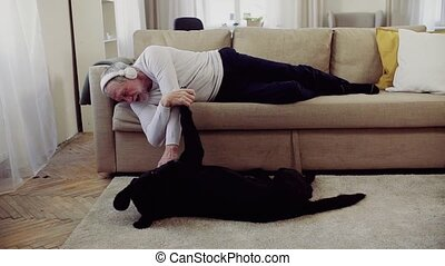 A happy senior man lying on a sofa indoors with a pet dog at...