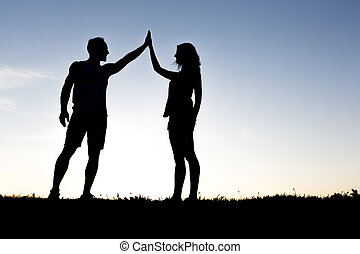 Happy silhouette couple holding up hands against the sky at dusk