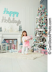 A happy smiling little girl is standing with Christmas presents near the New Year tree. Holiday and gifts 2018