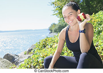 A happy sport woman with an apple