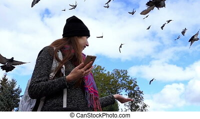A happy woman with a smartphone laughs while feeding doves in slo-mo
