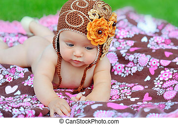 A happy young baby is sitting on green grass outside with bright clouds in the background.