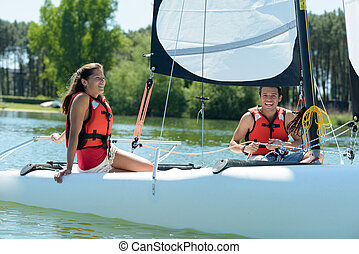 a happy young couple sailing