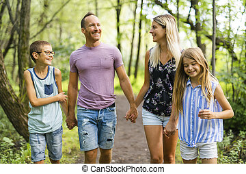 happy young family in forest having fun together