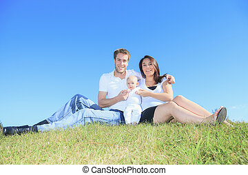 A Happy young family with little baby boy outdoors