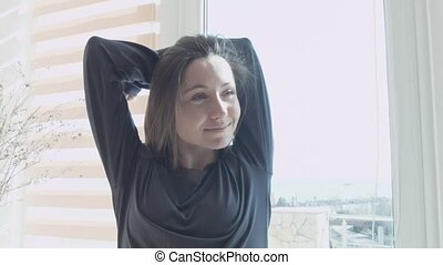 A happy young woman at the window in the sunlight pulls up...