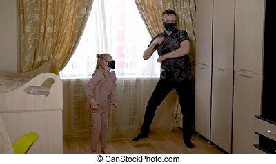 A happy young woman dancing with a cheerful native baby in a large living room in home clothes. On against a bright window. They are masked