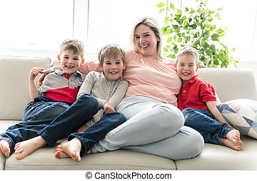 Happy young woman with children on sofa at home