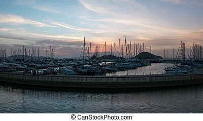 A harbour view at sunset. Yacht marina with night illumination. 4k, Time lapse.