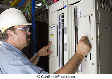 A hardhat worker ajusting the levels on the DC panel. Brands are removed and any readable items on the equipment irrevalent to real life.