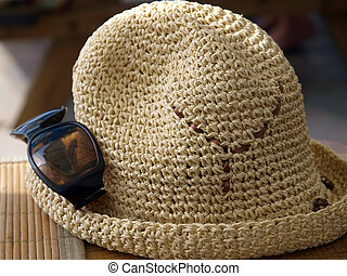 A hat and sunglasses - beach attributes