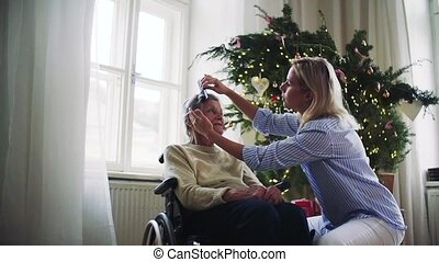 A health visitor combing hair of senior woman at home at...