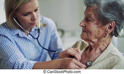 A health visitor examining a senior woman with a stethoscope at home.