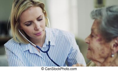 A young health visitor examining a senior woman with a stethoscope at home.