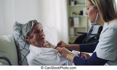 A health visitor examining a sick senior woman lying in bed...