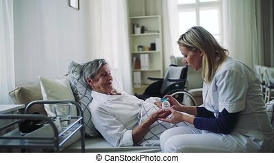 A health visitor giving pills to a sick senior woman lying...