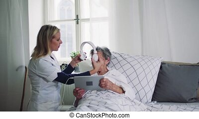 A health visitor helping a sick senior woman in bed at home.