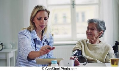 A health visitor measuring a blood pressure of a senior...