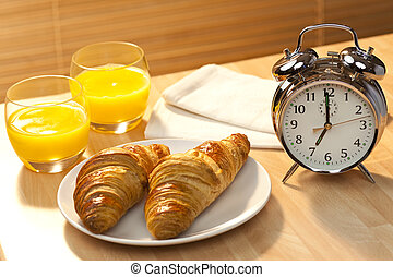 A healthy continental breakfast of croissant pastries, orange juice, oranges Illuminated with golden early morning sunshine and accompanied by a classic alarm clock set at 7am