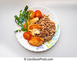 A healthy diet lunch with buckwheat, baked chicken and arugula on a round plate