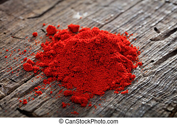 A heap of paprika powder, on wooden surface.