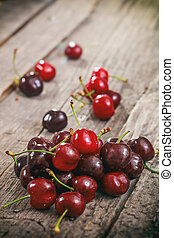 A heap of red cherries, on wooden surface.