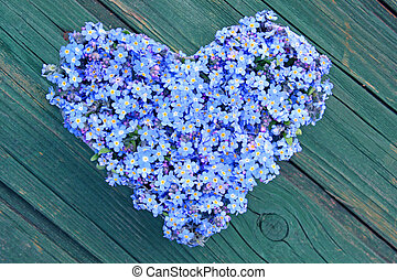 forget-me-not - a heart formed from forget-me-not on wooden...