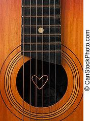 A heart lies on strings the guitar