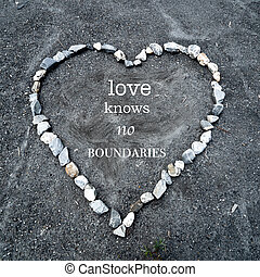 "heart made of colorful stones on sandy ground with the text ""love knows no boundaries"""