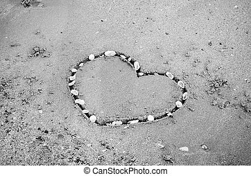 a heart on the sand in the beach black and white color tone style