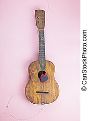 A heart on the torn strings of an old guitar. Unrequited love concept