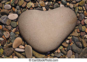 a heart-shaped stone on naturally polished color rock ...