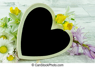 A heart with summer flowers on a wooden background