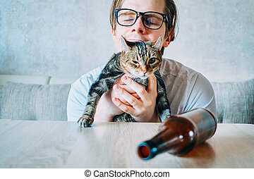 A heavily drunk man hugs a cat.