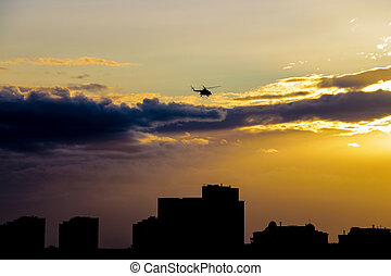 A helicopter flies over the city in the evening during sunset.