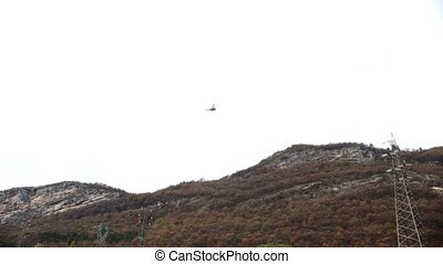 A helicopter flies over the mountains