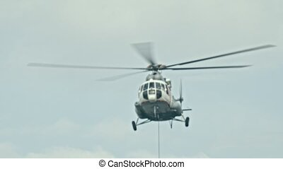 A helicopter flying in the sky at overcast weather - the cable hangs out of the helicopter