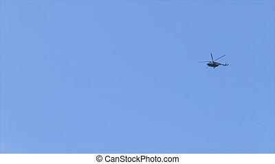 Lublin, Poland - April 2017: A helicopter hovering in the blue sky. Long shot.
