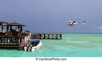 tropical island resort - a helicopter landing at tropical...