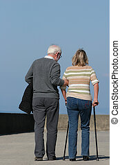 A Helping Hand - Elderly man helping a middle aged female to...