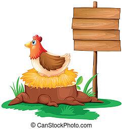 A hen near the empty wooden signboard