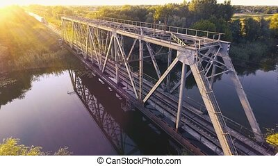 A high-speed train drives a bridge across the river at sunset