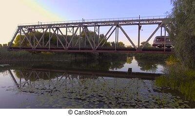 A high-speed train drives a bridge across the river. aerial...