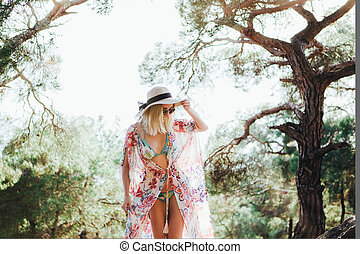 A hippie girl in a beautiful flying dress, hat and round glasses in a pine forest among the mountains.