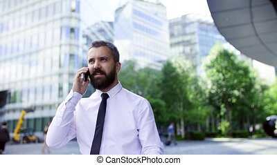 A hipster businessman with smartphone in the city, making a phone call.