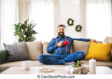 A hipster man with a red cup sitting on a sofa at home at Christmas time.