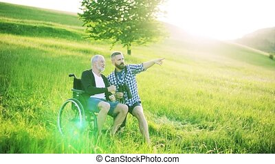 A hipster son and senior father in wheelchair using...