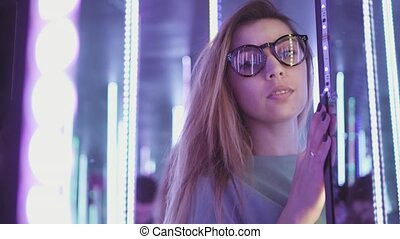 A hipster woman in stylish glasses stands in bright colored...